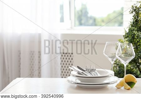 Set Of Clean Dinnerware And Lemon On Table Indoors. Space For Text