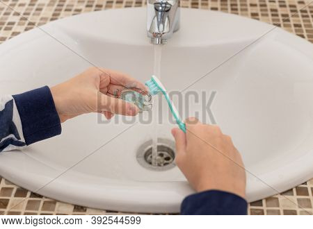 Childrens Hands Take Care Of The Removable Orthodontic Plate With Toothbrush Over The Bathroom Sink.