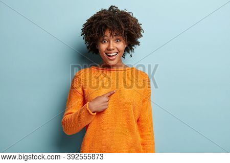 Good Looking Young African American Woman With Curly Hairstyle, Points At Herself, Wears Orange Jump