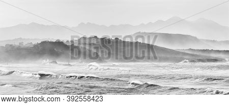 A Mountain Landscape In Silhouette With Beach And Waves Breaking In The Foreground