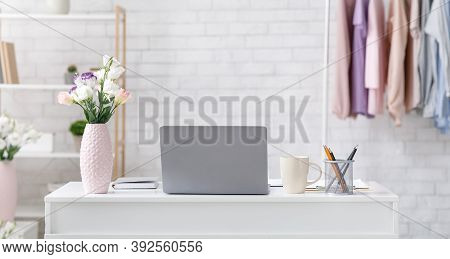 Modern Living Room Interior And Work From Home. Laptop, Vase With Flowers, Cup And Notepad On Table