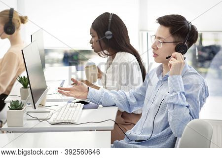 Frustrated Asian Helpdesk Operator Dealing With Clients Problem At Modern Call Centre. Technical Sup