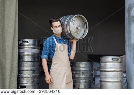 Work At Brewery During Coronavirus Pandemic And Industrial Craft Beer Plant. Young Attractive Worker