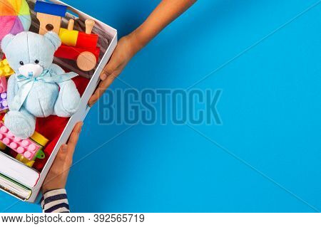 Donation Concept. Hands With Donate Box With Clothes, Books And Baby Kid Toys On Light Blue Backgrou