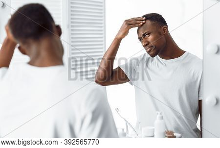 Hair Loss Problem. Concerned Black Guy Examining His Head Searching Gray Hair And Male-pattern Baldn