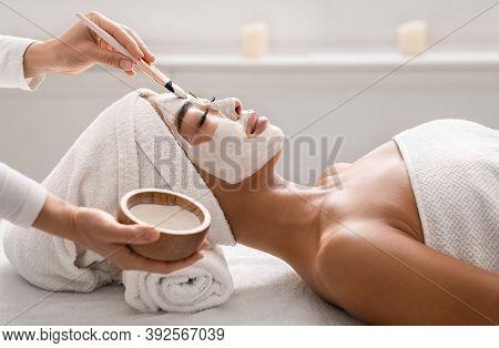 Facial Treatment. Beautician Applying Detox Clay Face Mask To Asian Woman At Spa, Young Korean Femal