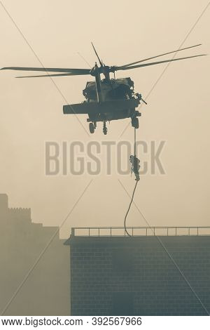 Military Combat And War With Helicopter Flying Into The Chaos And Destruction. Soliders Suspend From