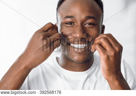Teeth Flossing. Portrait Of Happy Black Man Using Dental Floss Smiling To Camera Standing In Modern