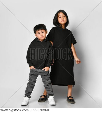 Stylish Brother And Sister Asian Children Posing In Front Of The Camera In The Studio On A White Bac