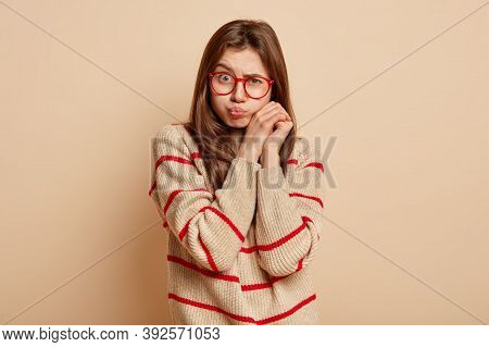 Upset Gloomy Woman Sulks Face, Raises Eyebrows, Has Folded Lips, Keeps Hands Together Near Face, Wea