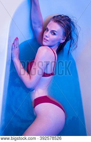 Sexy Girl In Bath. Spa. Bath Time. Body Washing. Hair Care. Neon Lights. Neon. Sexy Girl In Blue Bat