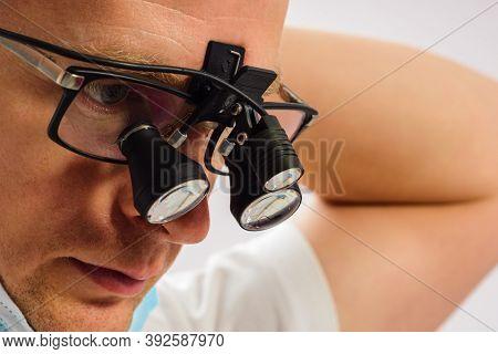 Dentist In Binoculars, Use Of Binoculars In Dental Treatment, Dentist In The Office, Magnifying Glas