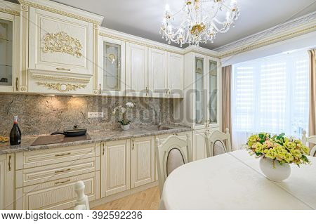 Luxury modern neoclassic beige kitchen interior, dining table and window