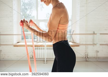Fit  Woman Working Out  With Elastic Band. Sportswoman Doing Stretching Exercises With Fitness Rubbe