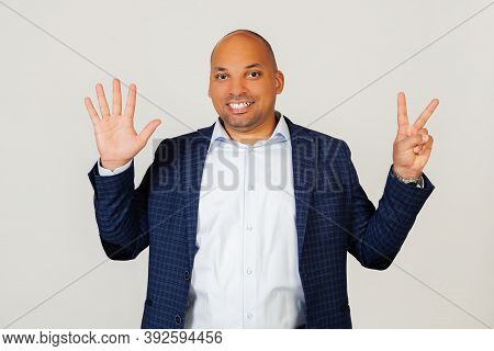 Portrait Of Successful Young African American Businessman Guy, Showing With Fingers To Number Seven,