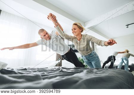Young Happy Couple Jumping On Bed And Make Fun While Sitting At Home. Family Fool Around At And Jump