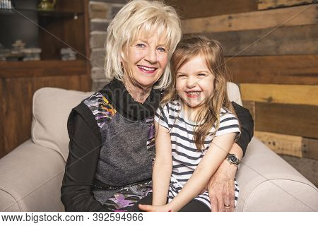 Portrait Of Grandmother With Their Little Child Sitting On Sofa At Home