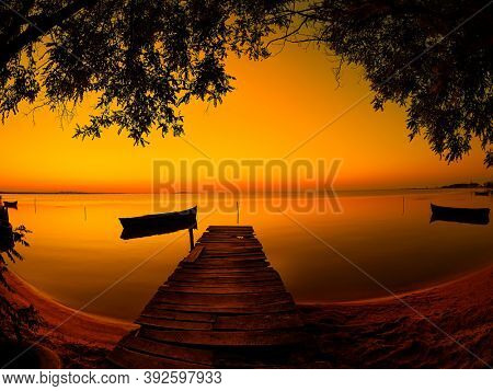landscape at sunset/sunrise by the lake with silhouette of fishing boat