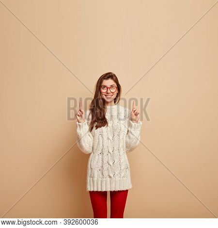 Photo Of Cheerful Lovely Woman With Straight Hair, Pleased Smile, Points Upwards At Free Space, Wear