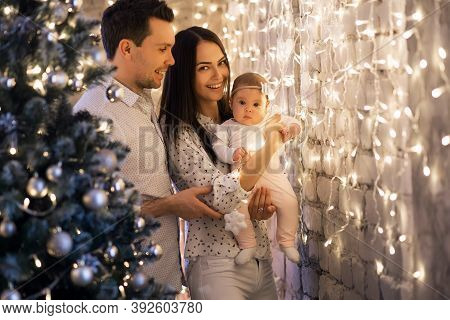 New Year Or Christmas, Portrait Of A Beautiful Family, Dad, Mom And Daughter Near The New Year Tree,