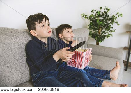 Two Happy Little Child Watching Tv And Eating Popcorn At Home