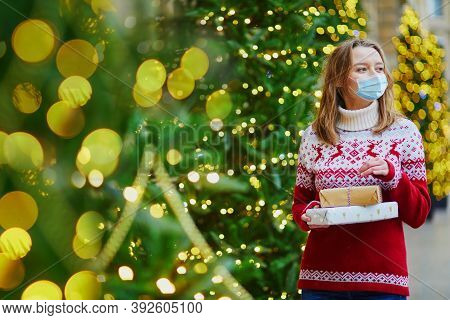 Happy Young Girl Wearing Face Mask In Holiday Sweater With Pile Of Holiday Gifts On A Street Of Pari