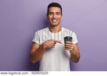 Youngster With Toothy Smile, Wears Casual White T Shirt, Points With Fore Finger At Takeaway Coffee,