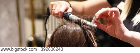 Hairdresser In A Beauty Salon Curls Curls With A Curling Iron. Woman Sitting In A Hairdresser In Fro