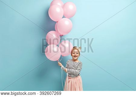 Playful Cheerful Little Smiling Kid Wears Princess Crown, Smiles Broadly, Carries Balloons, Being On