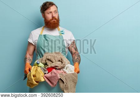 Busy Male Works About House, Holds Basin With Clean Towels And Bottle Of Detergent, Wears Blue Apron