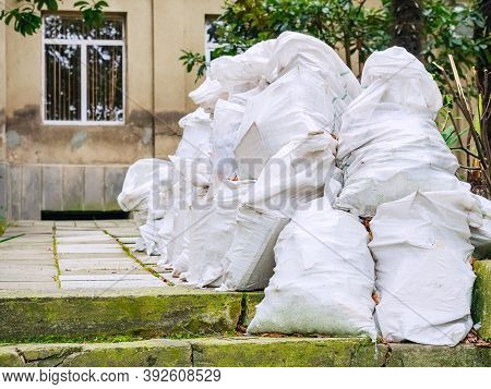 Many Identical White Bags With Unnecessary Old Rubbish Are Piled Up Near The House