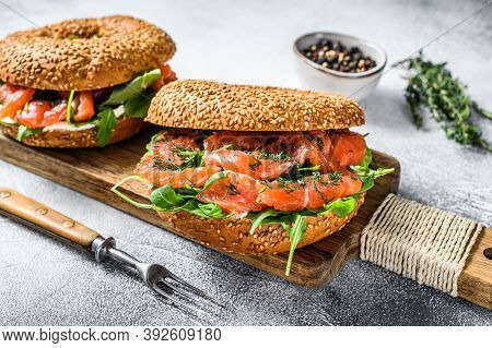 Smoked Salmon Bagels Sandwich With Soft Cheese And Arugula On A Cutting Board. White Background. Top