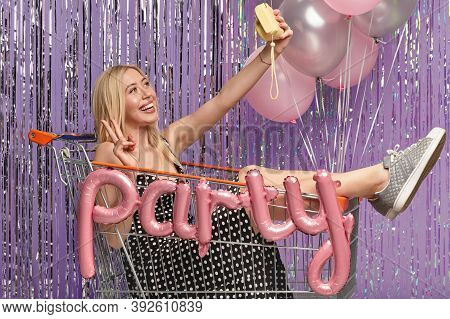 Photo Of Happy Fashionable Girl Fools Around At Party, Poses At Shopping Cart, Makes Peace Gesture A