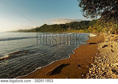 Pacific Coast Of Costa Rica In Central America, Evening Sunset With Palm Trees, Ocean And Clouds On