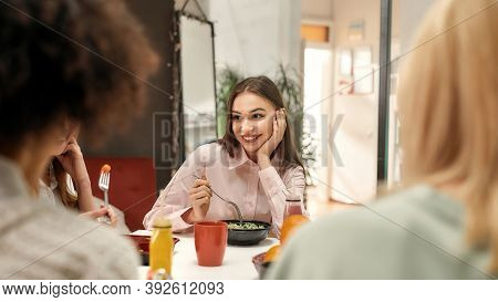 Business Lunch. A Fashionably Dressed Young Brown Haired Woman Smiling And Sitting At A Table With H