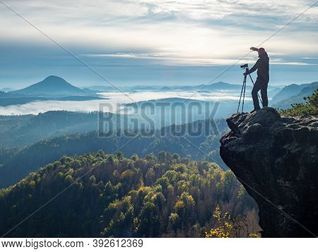 Professional On Cliff. Nature Photographer Hold Tripod With Camera. Man At Sunrise At Open View On M