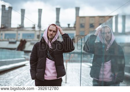 Handsome Casual Man In Windbreaker Standing On A The Soaring Bridge Industrial Background