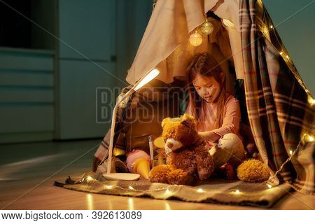 A Little Girl Sitting On A Floor Cross-legged Barefoot In A Self-made Hut Made Of A Plaid, Making A
