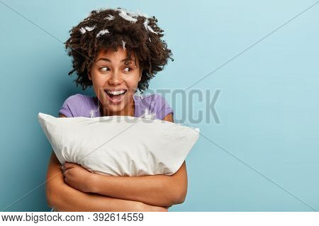 Photo Of Optimistic Dark Skinned Woman With Curly Hair, Embraces Soft Pillow, Has Good Mood After Af