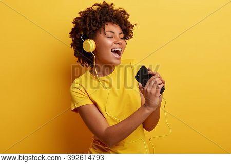 Joyful Optimistic Glad Black Woman Glad To Search Favourite Composition On Web Page, Listens Favouri