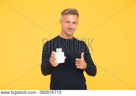 Product Publicity. Happy Man Hold Perfume Pointing Gun Hand Gesture Yellow Background. Skin Care Cos