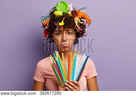 No Plastic Pollution Concept. Unhappy Dark Skinned Woman Has Dejected Look, Frowns Face, Holds Colou