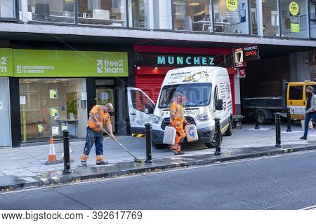 Doncaster, Yorkshire, England - October 7, 2020. Male Workers With Orange Vests Cleaning The Street