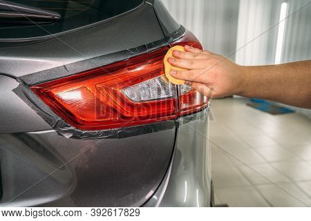 Worker Hand Polishes Headlight With Sponge And Wax Polish Paste, Restoration Of Headlights In Car De