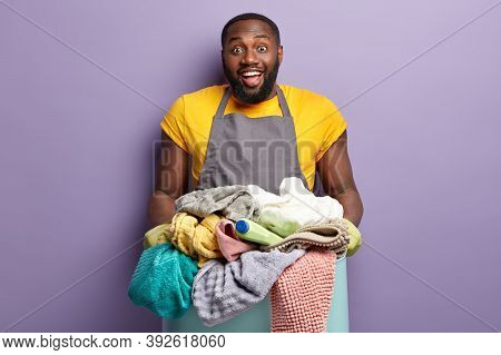 Headshot Of Glad Dark Skinned Man With Thick Bristle Smiles Gladfully, Holds Heap Of Unfolded Laundr