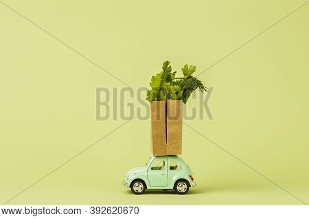Irkutsk, Russia - October 3, 2020: Light Green Retro Toy Car Carries Paper Shopping Bags With Fresh