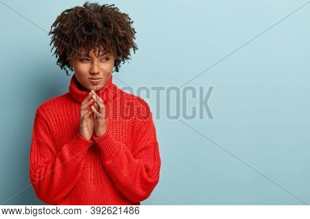 Pensive Black Young Woman Strategist Has Great Plan, Holds Hands Together, Looks Curiously With Inte
