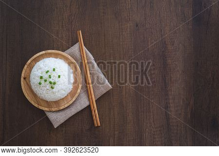 Cooked White Rice In A Wooden Dish With Green Onion Sliced On Top With Chopsticks And Placemat On A
