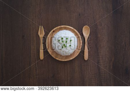 Cooked White Rice In A Wooden Dish With Green Onion Sliced On Top With Wooden Spoon, Wooden Fork On