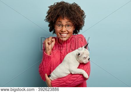 Triumphing Successful Afro American Woman Clenches Fist, Has Toothy Smile, Holds Pedigree Dog Of Smo
